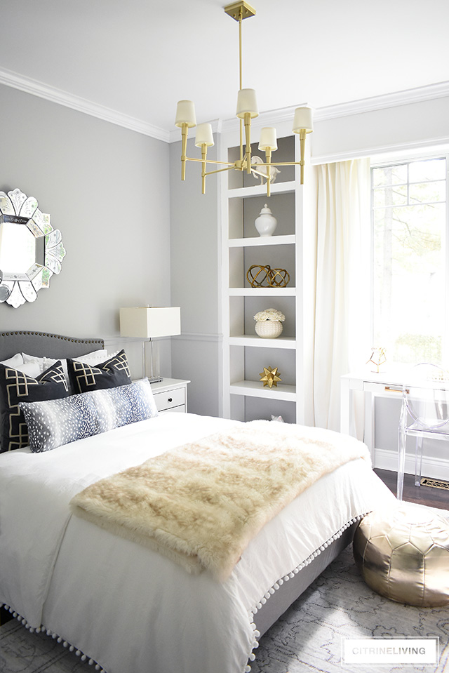 A fabulous fashion-forward teen girl bedroom makeover with chic and elegant details - grey upholstered bed with brass nailhead trim, soft layers of pompom bedding with added texture and pattern and a chic brass chandelier to complete the look!