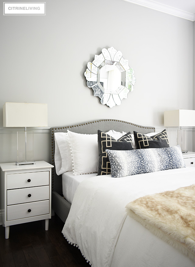 Gorgeous teen girl bedroom makeover featuring a beautiful and tailored grey upholstered bed with brass nailhead trim, venetian style mirror and glam crystal table lamps. Layers of pattern and textured on the upholstered bed are fashion-forward and chic!