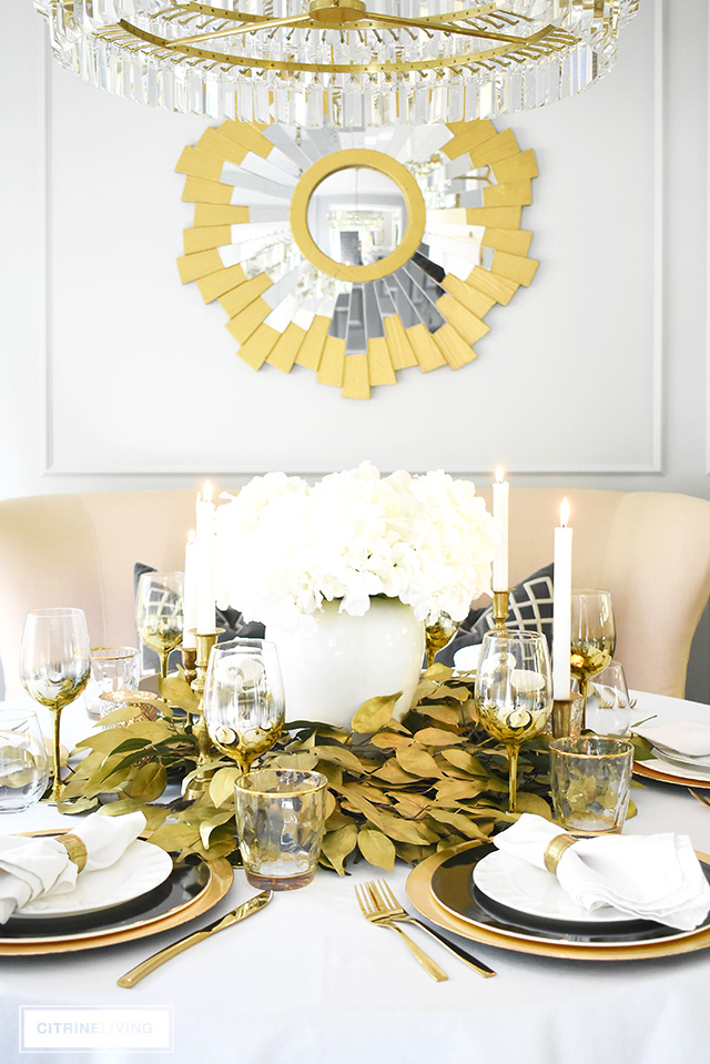 Beautiful luxe fall tablescape with an elegant centrepiece using faux hydrangeas and gold leaf picks. Black and white dishware are chic and sophisticated!