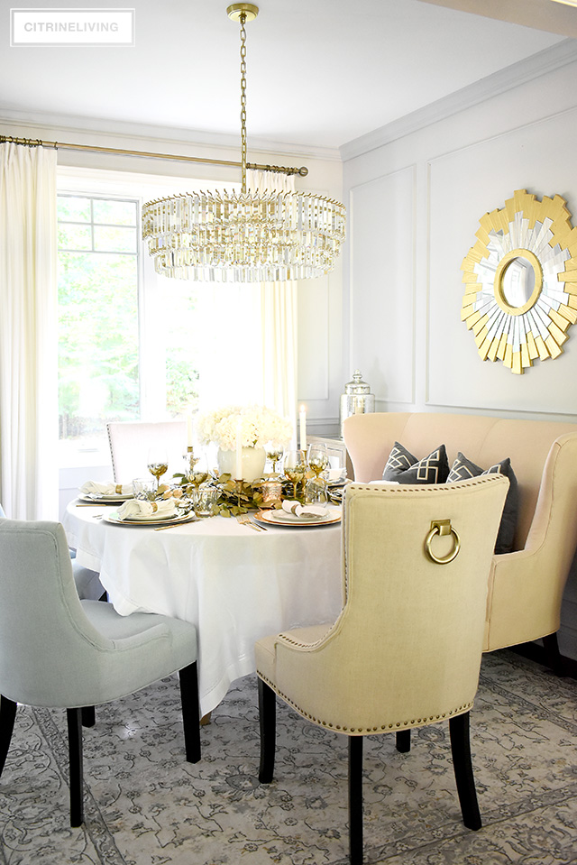 Beautiful luxe fall tablescape set in a light and airy dining room - crystal chandelier, gold mirror, vintage style light grey rug.