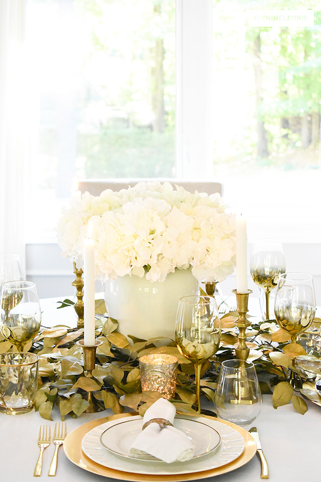Beautiful luxe fall tablescape using faux gold leaves surrounding an elegant arrangement of faux white hydrangeas. Gold accents throughout the table are elegant and sophisticated!