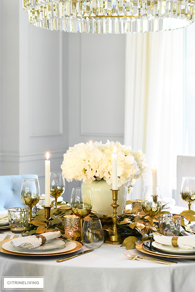 Beautiful luxe fall tablescape with gold charger plates, flatware and wineglasses - accented with white and black dishes for an understated glam feel.