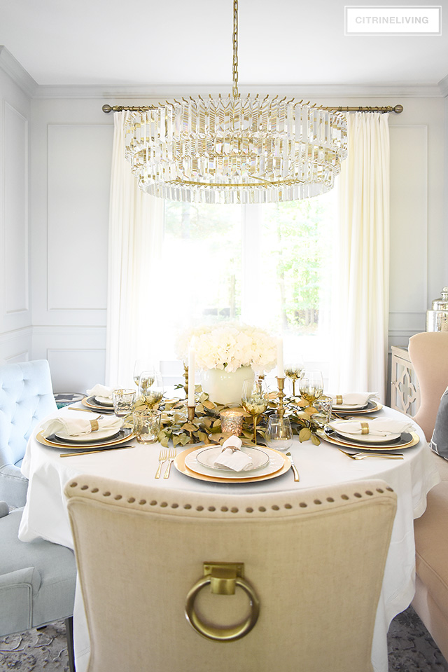 Beautiful luxe fall tablescape with white hydrangeas, gold faux leaves and white and black dishes for an upscale look.