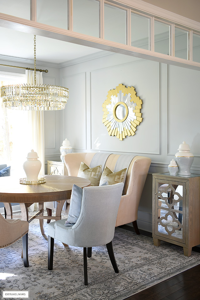Chic dining room decorating - a classic, vintage style rug, crystal chandelier, upholstered settee and gold sunburst mirror are sophisticated and timeless!