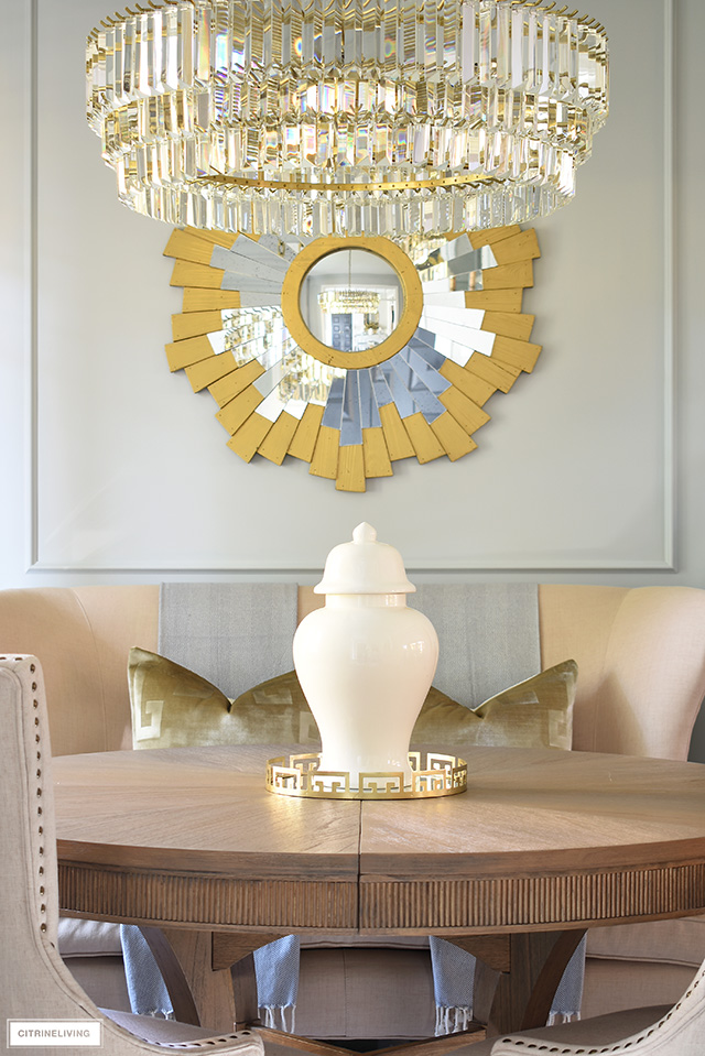 Sophisticated and chic dining room decor - crystal chandelier, gold sunburst mirror and classic ginger jars.