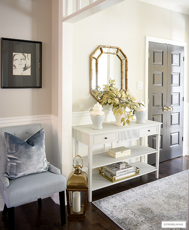 Fall entryway console table with chic ginger jars, faux gold leaves, gold mirror, gold tray, decorative box.