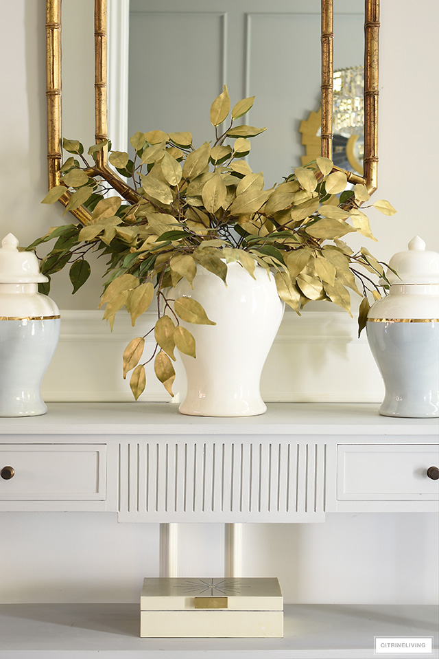 Simple and chic fall entryway decor with faux gold leaves and ginger jars.