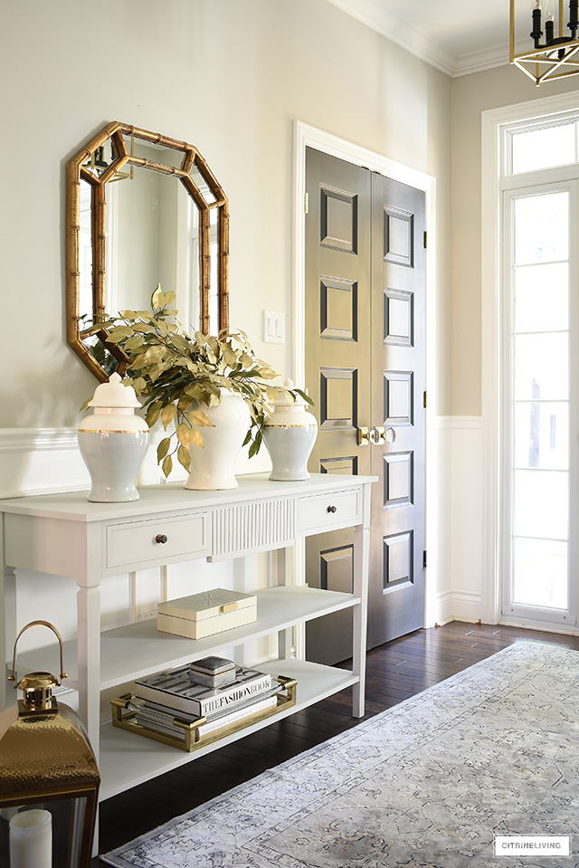 Elegant fall entryway styled with sophisticated ginger jars, faux gold leaves and gold and white accessories.