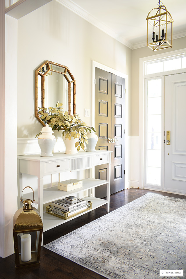 Console table styled with elegant fall decor. Ginger jars, faux gold leaves, gold/lucite tray, design books.