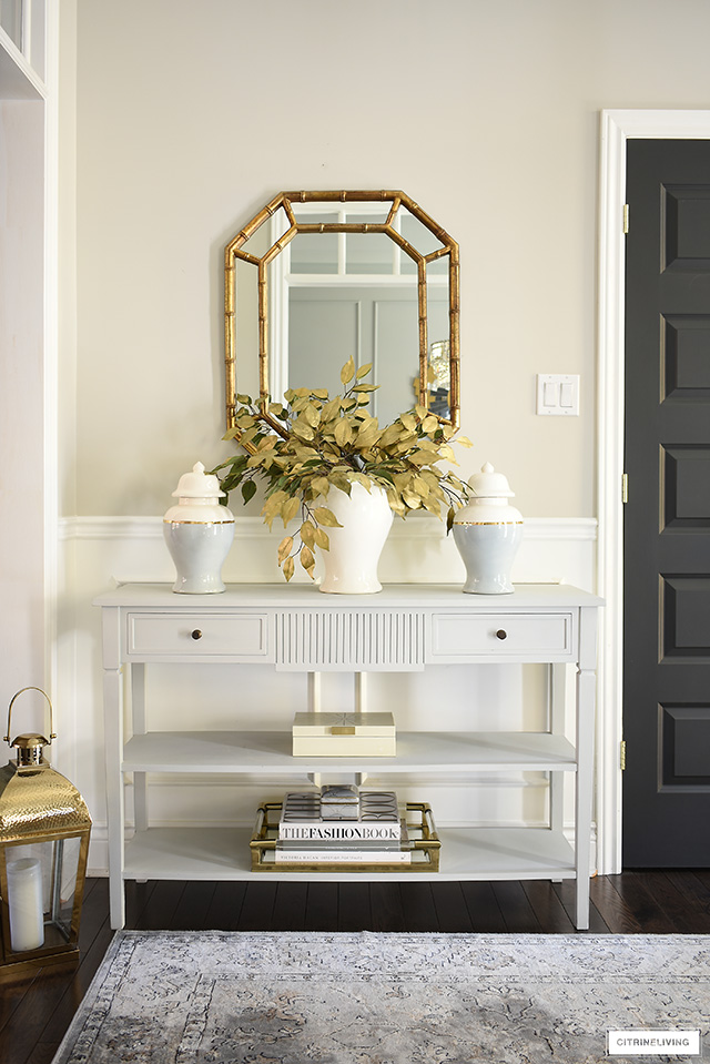 Gorgeous fall entryway table styled with faux gold leaves, ginger jars, decorative box, brass + lucite tray.