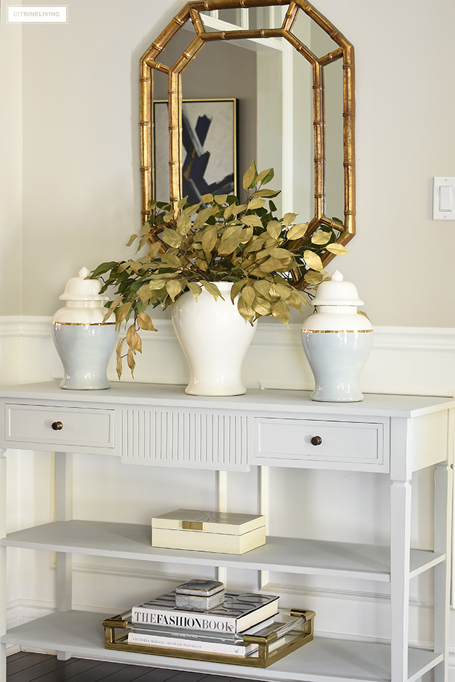 Beautiful fall console table styling ideas - gold handprinted faux leaves, ginger jars, brass+lucite tray with design books.