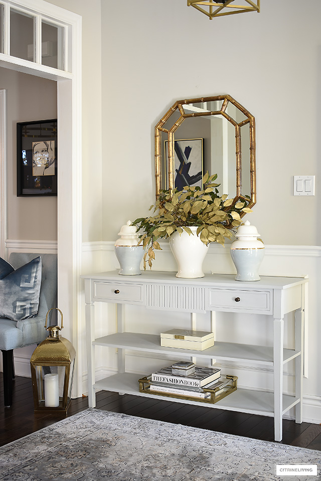 Fall entryway decorating - simple console table styling with ginger jars, faux gold leaves, design books and decorative box.
