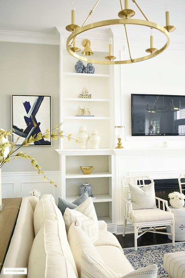 Elegant Fall living room with beautifully decorated bookshelves - ginger jars, gold accents and warm neutrals. are the perfect combination for setting the seen.