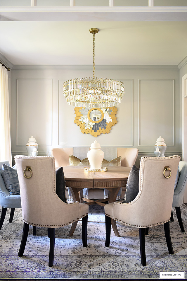 Elegant dining room decorating with classic elements - crystal chandelier, gold sunburst mirror, vintage style rug and classic ginger jars.