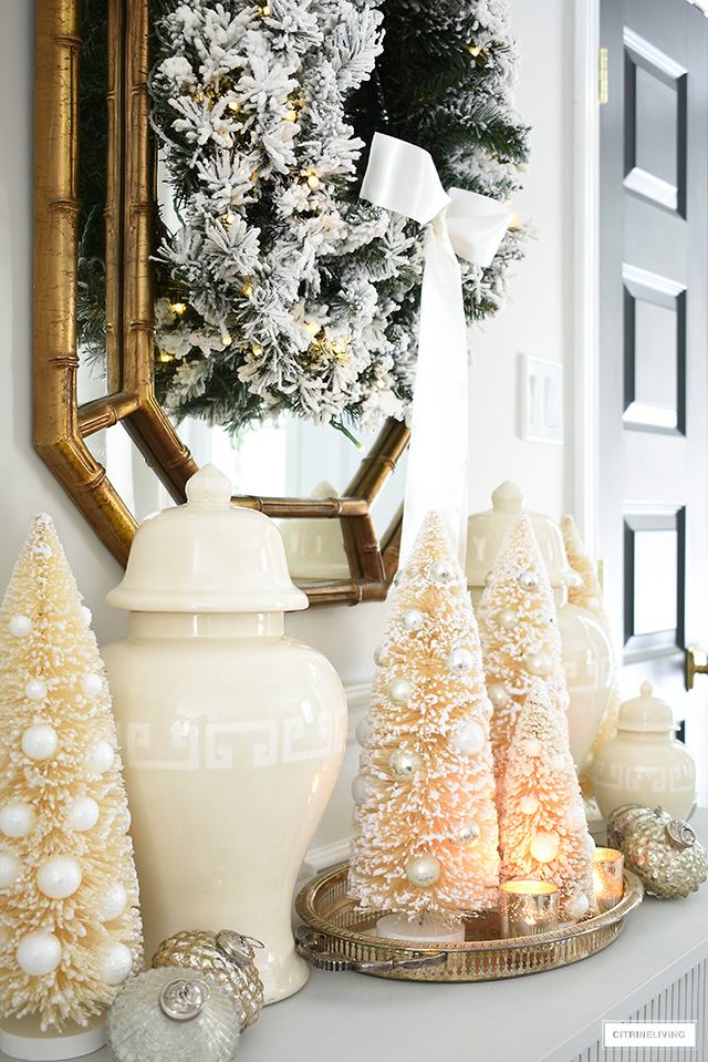 Create an elegant and welcoming Christmas entryway with a flocked streak, bottle brush trees, ginger jars and mercury glass ornaments.