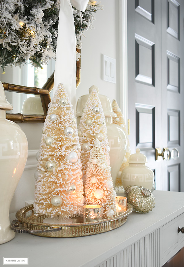 Beautiful bottle brush trees clustered together set the scene in this elegant and welcoming Christmas entryway.