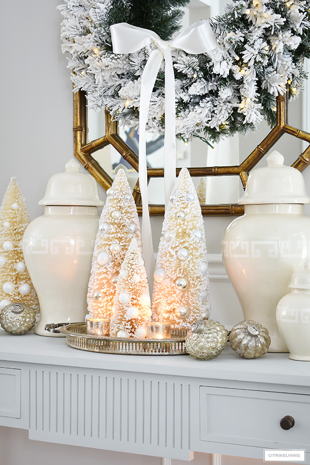 Create an elegant and welcoming Christmas entryway with ginger jars and bottle brush trees.