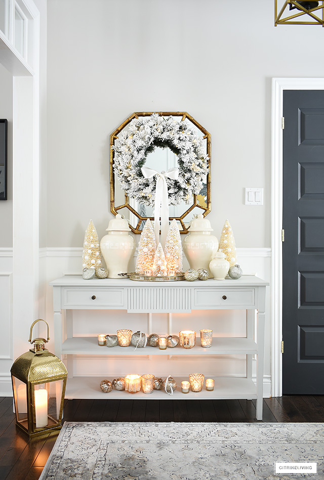 And elegant and welcoming Christmas entryway styled with bottle brush trees, ginger jars and mercury glass candles.