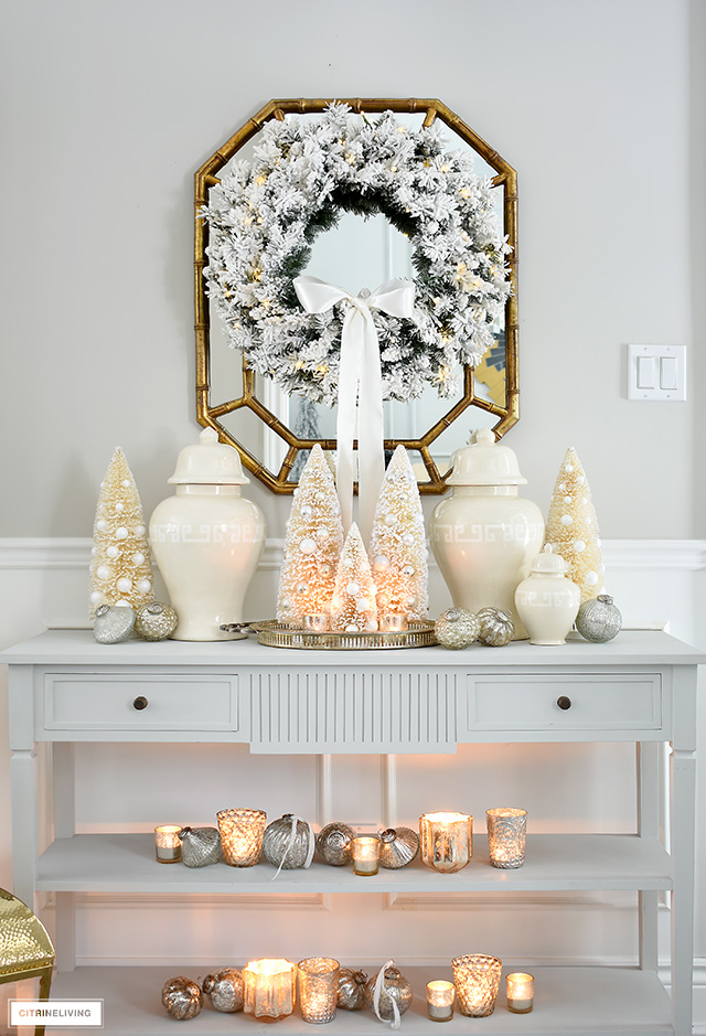 Elegant and welcoming Christmas entryway with ginger jars, bottle brush trees and mercury glass ornaments and candles.