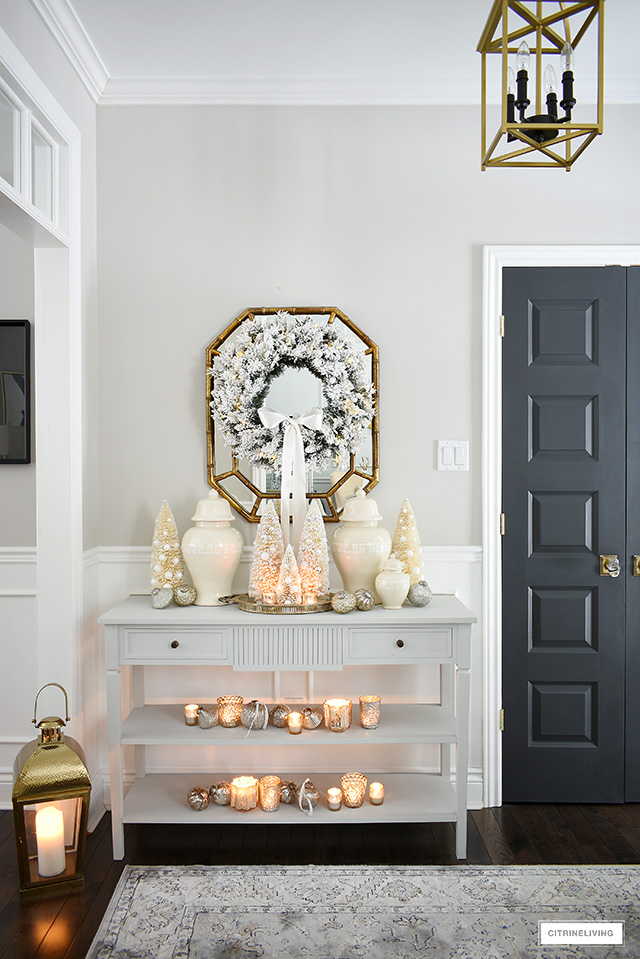 A flocked wreath, ginger jars, bottle brush trees and mercury glass ornaments and votives set the scene for this elegant and welcoming Christmas entryway!