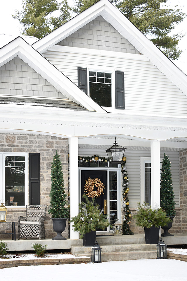 Front porch decorated for Christmas with elegant outdoor decor.