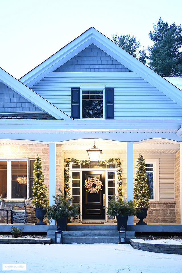 Christmas porch with beautiful pencil trees flanking the front steps, gold wreath and decorated garland.