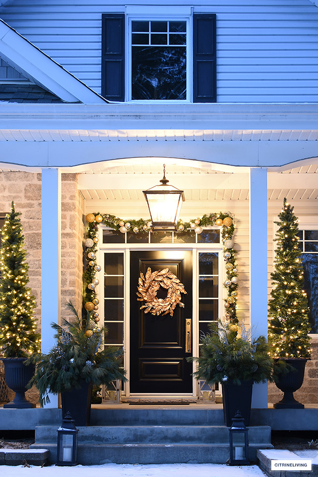 Elegantly decorated Christmas porch with lit pencil trees, garland and gold magnolia wreath.