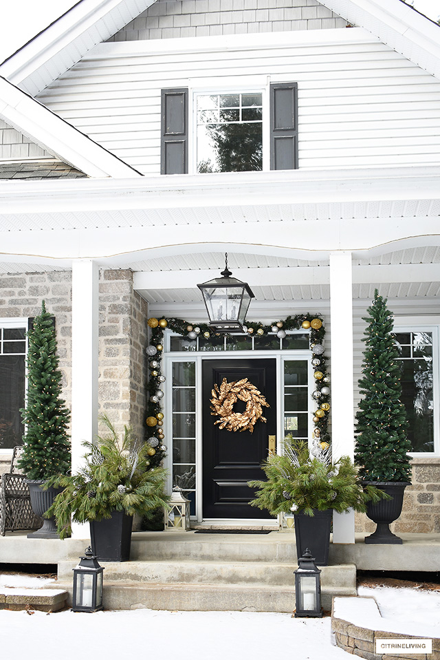Front porch with gold and silver outdoor Christmas decorations.