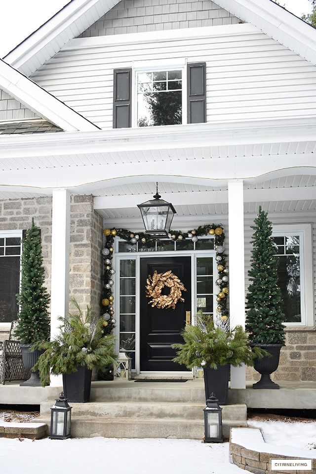 Christmas front porch with garland, gold wreath, pencil trees and fresh cut pine arrangements.