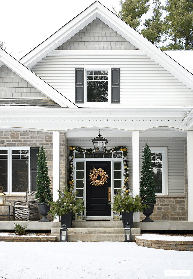 Elegant front porch decorated for Christmas with pencil trees, gold magnolia wreath and fresh pine arrangements.