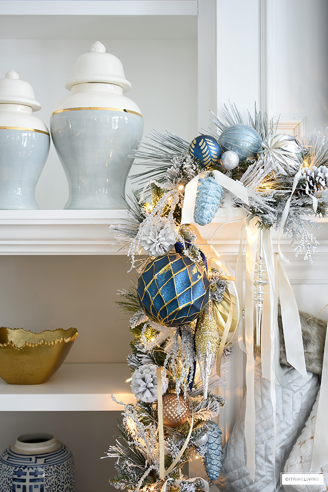 Christmas mantel with flocked garland, blue and gold decorations, ginger jars