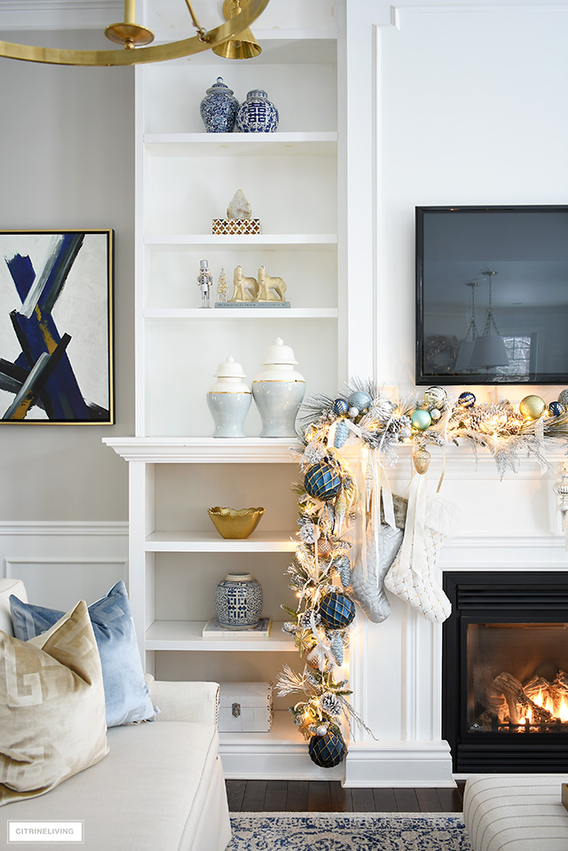 Elegant Christmas living room - Christmas mantel with flocked garland, blue and gold decorations, builtin bookshelves