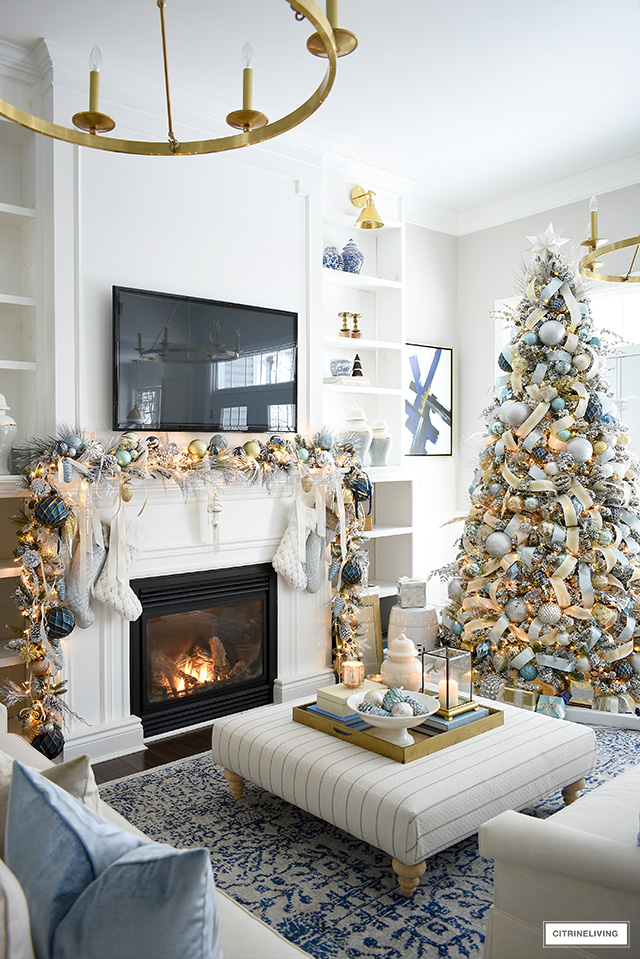 Elegant Christmas living room decor with light blue and gold color palette.