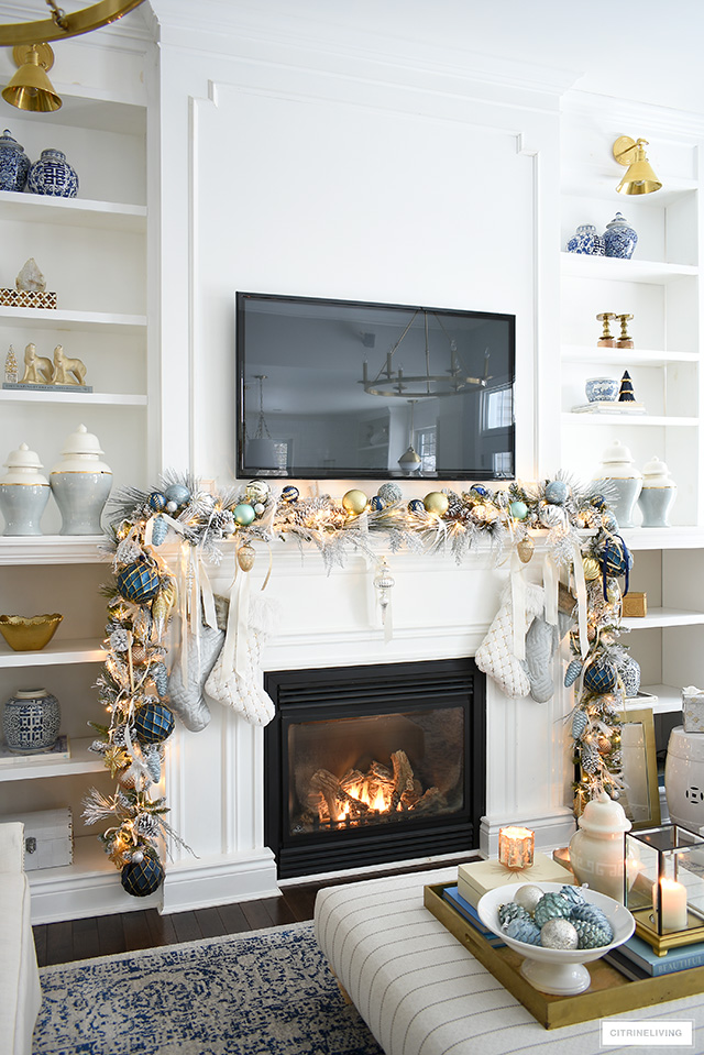Elegant Christmas living room - Built-in bookshelves, christmas mantel with flocked garland and stockings.