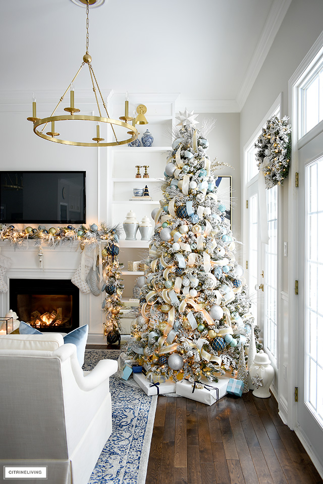 Christmas living room decorating ideas, flocked tree and garland with blue and gold decor.