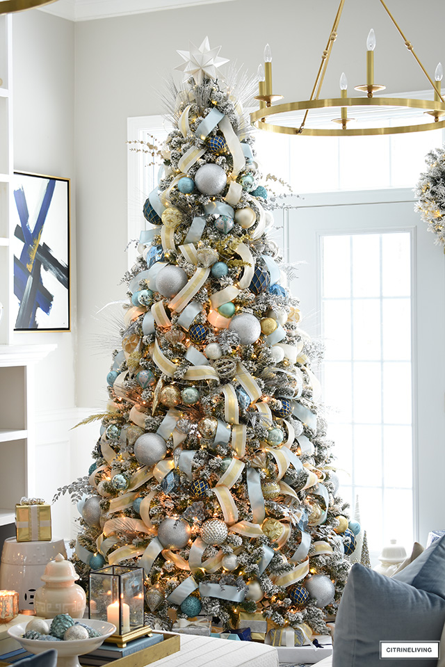 Elegant Christmas living room - Beautiful flocked Christmas tree with blue and gold decorations and ribbon.