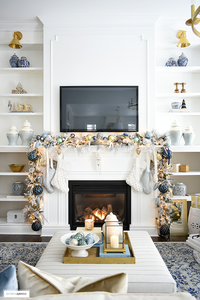 Elegant Christmas living room - Gorgeous Christmas mantel with flocked garland, light blue and gold decorations.