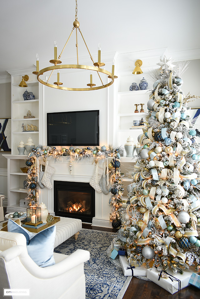 Elegant Christmas living room - Flocked Christmas tree and garlands with light blue and gold decorations