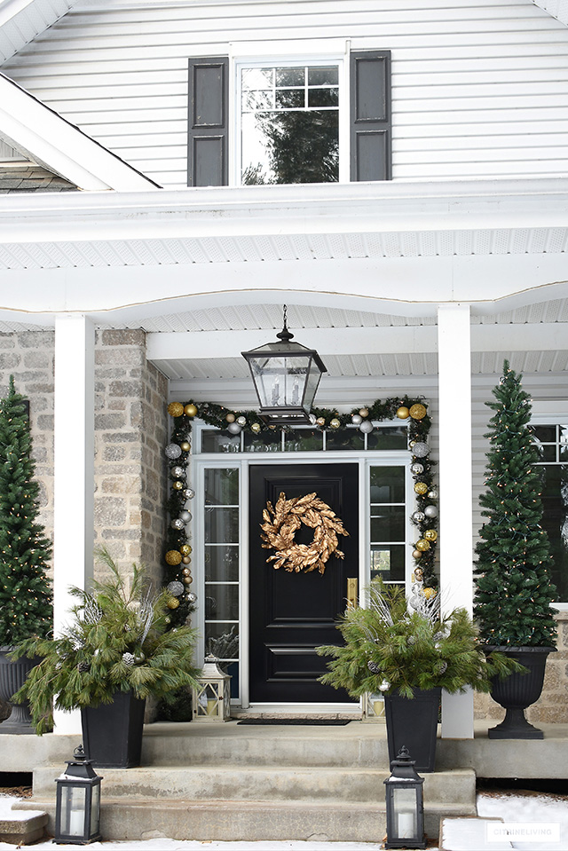 Christmas decorated porch with garland, pencil trees and pine arrangements.