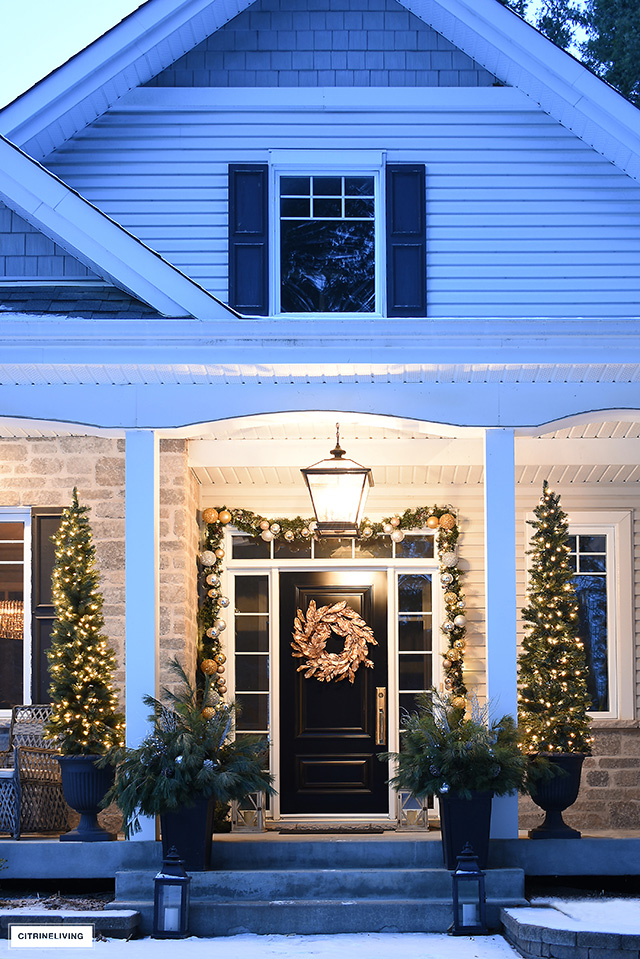 Beautiful nighttime porch with Christmas pencil trees, gold magnolia wreath and decorated garland.