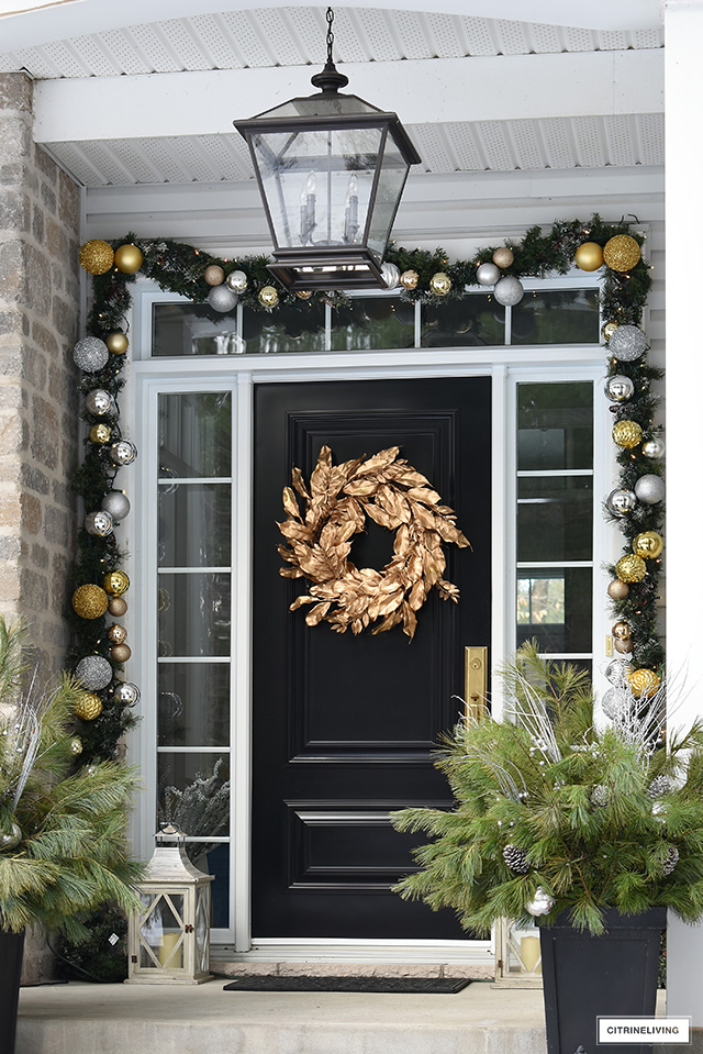 Christmas decorated front porch with gold magnolia wreath and garland with silver and gold ornaments.