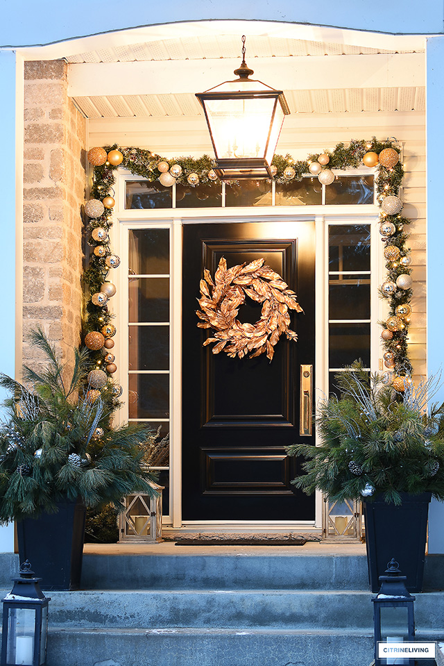 Front steps with oversized pendant light, god Christmas wreath and decorated garland.