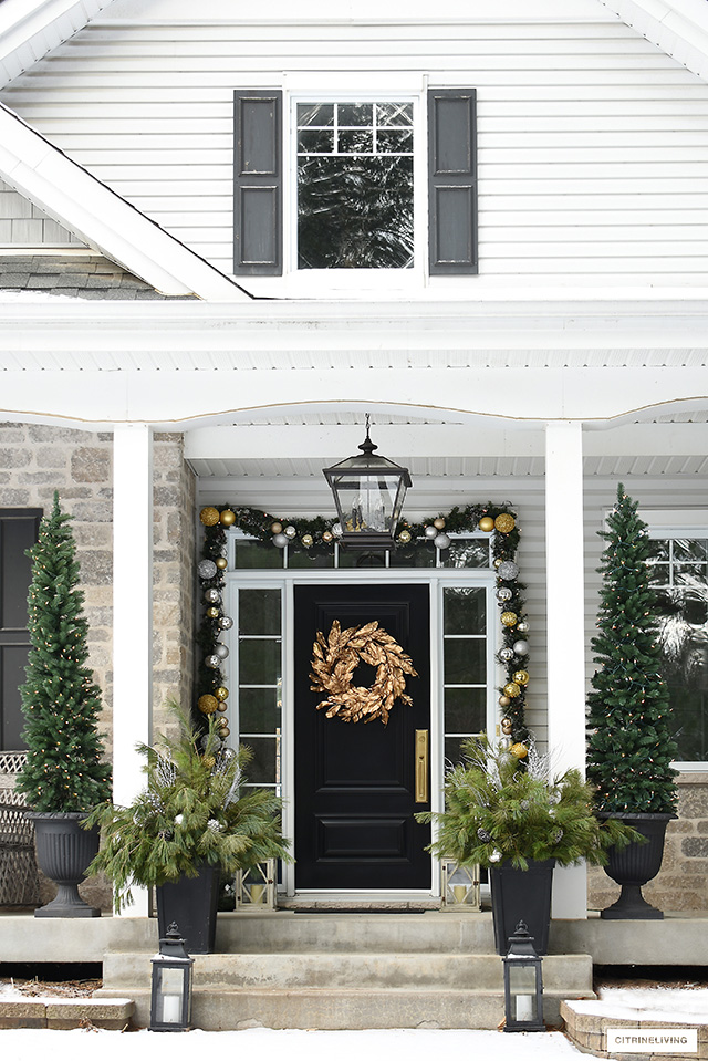 Gorgeous Christmas porch using garland decorated with silver and gold ornaments.