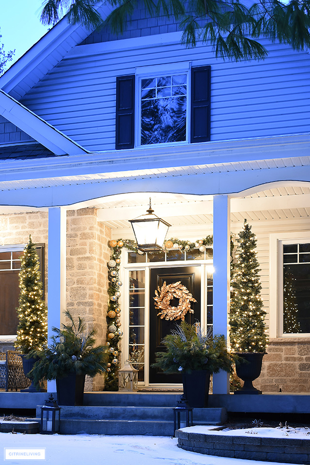 Front porch lit at night with beautiful Christmas decorations.