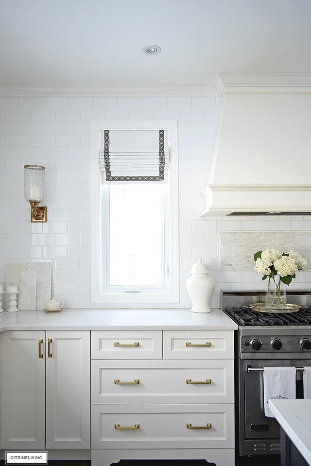 White kitchen with brass hardware, custom rangehood, roman blinds on windows.