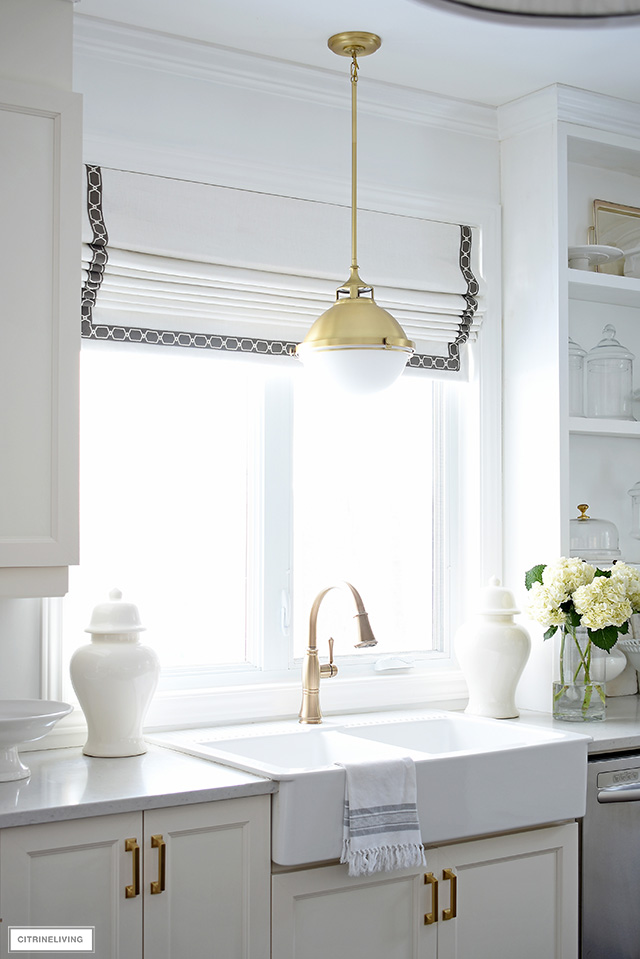 White farm sink with brass faucet and pendant light and custom Roman shade window covering.