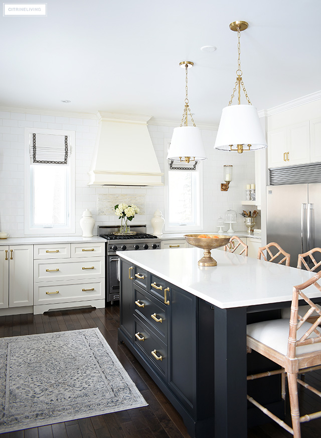 Traditional white kitchen with black island, brass hardware and lighting, vintage style rug and custom roman shades.