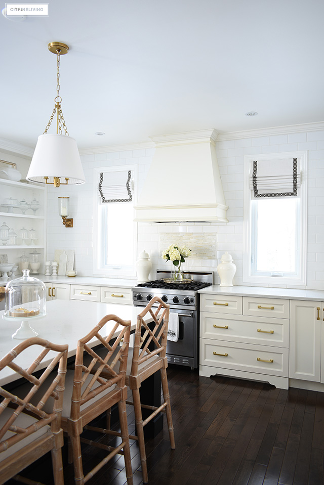 Traditional kitchen with brass accents, Chinese Chippendale stools and custom roman shades on windows.