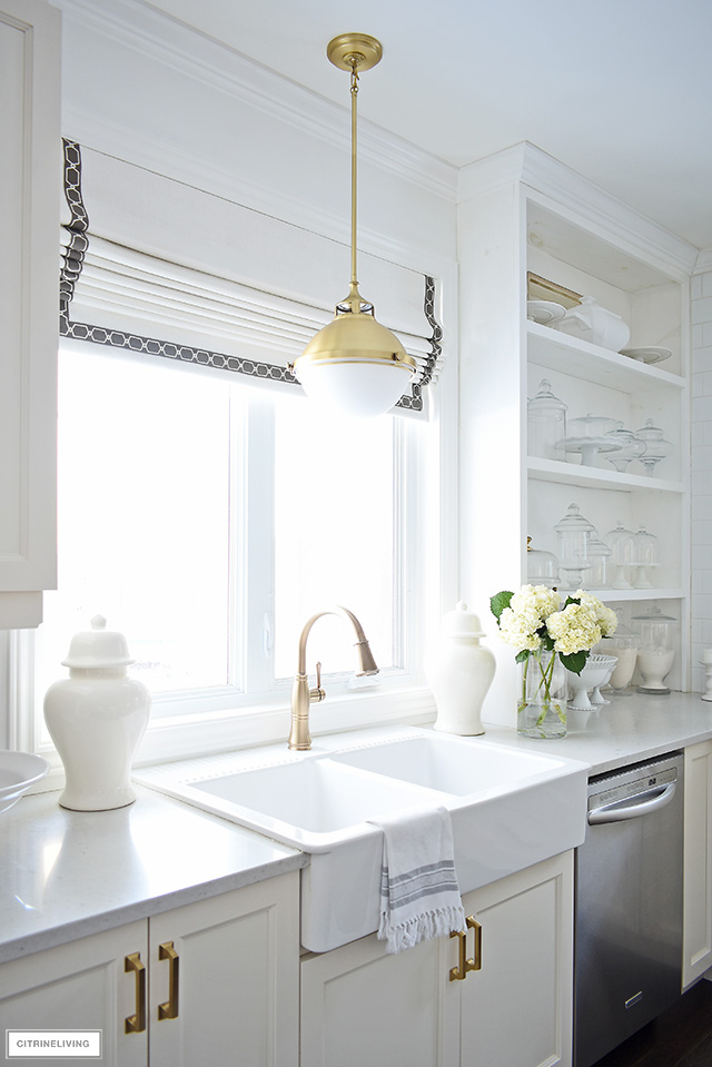 White farm sink with brass faucet and pendant light and custom Roman shade window covering. Open shelves with white and glass accessories.