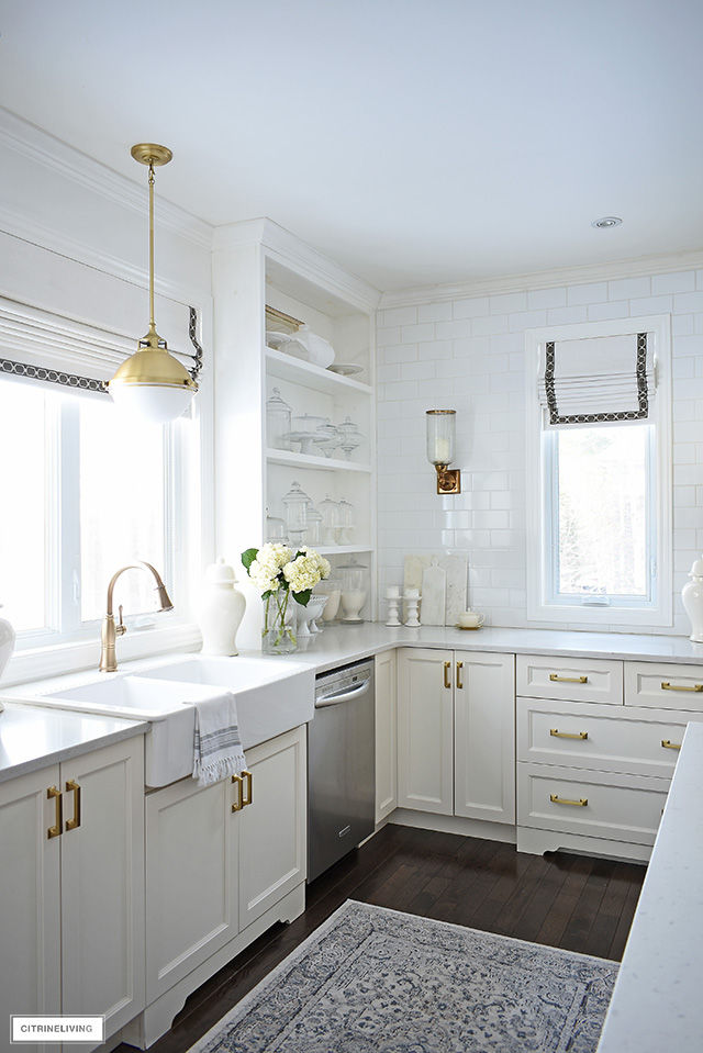 Kitchen with ivory cabinets, brass hardware and lighting, open shelves with white and glass accessories. Custom roman shades on windows.